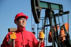Trabajador de la industria de petróleo que sostiene la almádena al lado de la bomba Jack. imágenes de archivo libres de regalías