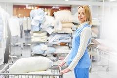 Trabajador de la muchacha que sostiene un carro de lavadero con las almohadas limpias imagen de archivo