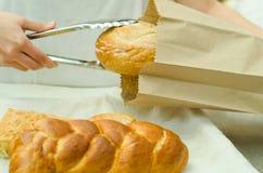 Trabajador de la panadería que coloca la barra de pan dentro de la bolsa de papel marrón usando las pinzas de plata grandes Foto de archivo libre de regalías