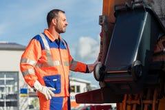 Trabajador de la recolección de basura que pone el compartimiento en el camión inútil foto de archivo libre de regalías