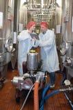 Trabajador de la redecilla que trata de los barriles en fábrica interior del winemaker fotografía de archivo