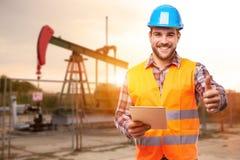 Trabajador de la refinería que se coloca delante de la bomba de aceite imagen de archivo