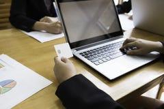 Trabajador de la señora co que usa la tarjeta del ordenador portátil y del control a disposición en área de trabajo fotos de archivo libres de regalías