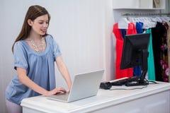 Trabajador de la tienda que usa el ordenador portátil por hasta imagenes de archivo
