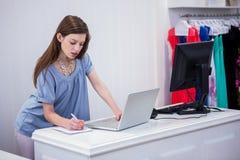 Trabajador de la tienda que usa el ordenador portátil por hasta fotos de archivo libres de regalías