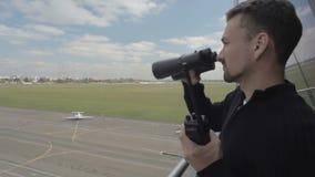 Trabajador de los prismáticos y de la radio portátil del uso del aeropuerto que se colocan en torre de control almacen de video