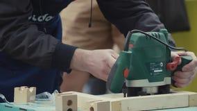 Trabajador de madera de la cámara lenta que usa el taladro o el dispositivo del trazador que trabaja en la madera, polvo de la si almacen de video