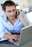 Trabajador de Ministerio del Interior que usa la computadora portátil Imagen de archivo