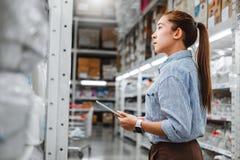 Trabajador de mujer asiático que trabaja con las cajas de comprobación digitales de la tableta paquetes logísticos de las fuentes imagen de archivo