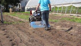 Trabajador de mujer que conduce la unidad del tractor del rototiller que prepara la semilla del suelo almacen de metraje de vídeo