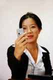 Trabajador de mujer que controla su teléfono Imágenes de archivo libres de regalías
