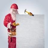 Trabajador de Santa Claus en casco con el cartel Imagen de archivo