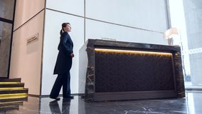 Trabajador de sexo femenino amistoso del hotel que camina a la estación de deber almacen de metraje de vídeo