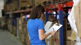 Trabajador de sexo femenino con el tablero en Warehouse almacen de video