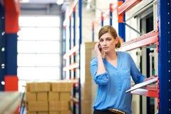Trabajador de sexo femenino de la logística en el teléfono móvil en almacén Imágenes de archivo libres de regalías
