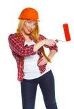 Trabajador de sexo femenino divertido del contruction en un casco con el rodillo a disposición Imagen de archivo