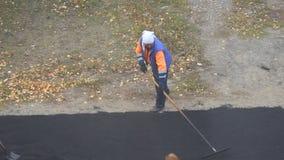 Trabajador de sexo femenino durante la carretera de asfalto Trabajo manual femenino pesado en la construcción almacen de metraje de vídeo