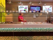 Trabajador de sexo femenino en el yogurtland Vendedor del helado fotos de archivo