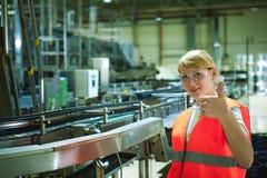 Trabajador de sexo femenino en fábrica de la cerveza mujer del retrato en el traje, colocándose en la línea producción alimentari imagenes de archivo