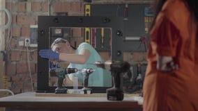 Trabajador de sexo femenino en la fábrica de los muebles que prueba el destornillador del taladro La mujer con los tatuajes a man almacen de metraje de vídeo