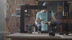 Trabajador de sexo femenino en la f?brica de los muebles que prueba el destornillador del taladro Profesi?n del carpintero Fabric metrajes