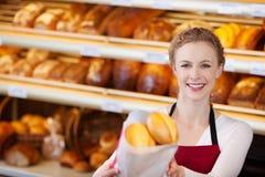 Trabajador de sexo femenino feliz que da el bolso de panes Foto de archivo libre de regalías
