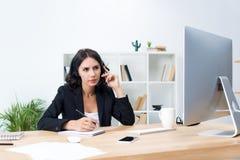 trabajador de sexo femenino joven concentrado del centro de atención telefónica con las auriculares Imagen de archivo