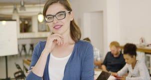 Trabajador de sexo femenino joven que presenta en oficina almacen de video