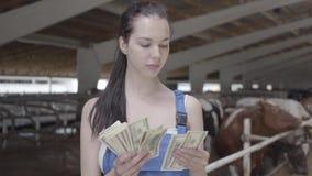 Trabajador de sexo femenino lindo del granjero del retrato en la granja de la vaca que cuenta efectivo El granjero positivo consi metrajes