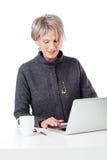 Trabajador de sexo femenino mayor que usa un ordenador portátil Foto de archivo libre de regalías