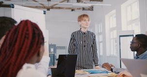 Trabajador de sexo femenino milenario joven feliz del interno de la oficina que habla al equipo multiétnico en la reunión del p almacen de metraje de vídeo