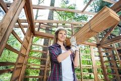 Trabajador de sexo femenino pensativo que lleva tablones de madera fotos de archivo