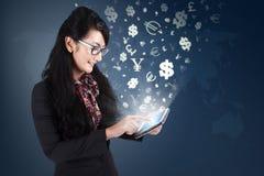Trabajador de sexo femenino que hace el dinero con la tableta Fotos de archivo libres de regalías