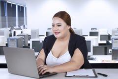 Trabajador de sexo femenino que mecanografía en el ordenador portátil Foto de archivo
