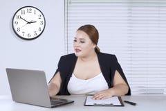 Trabajador de sexo femenino que trabaja con el ordenador portátil Foto de archivo libre de regalías