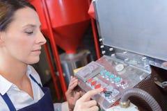 Trabajador de sexo femenino que usa la máquina en la fábrica Imágenes de archivo libres de regalías