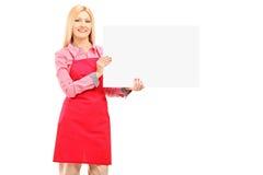 Trabajador de sexo femenino sonriente que lleva un delantal y sostener un panel Fotografía de archivo