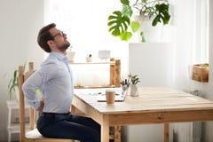 Trabajador de sexo masculino cansado que estira en el sufrimiento de la silla del dolor de espalda imagenes de archivo
