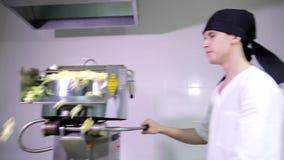 Trabajador de sexo masculino caucásico atractivo joven de la cocina en el pañuelo principal negro que espera el trabajo con la má metrajes