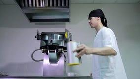 Trabajador de sexo masculino caucásico atractivo joven de la cocina en el pañuelo principal negro que llena la máquina de las pal almacen de video