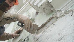 Trabajador de sexo masculino caucásico puesto en la pared uniforme anaranjada de los yesos con la herramienta de la espátula almacen de metraje de vídeo