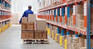 Trabajador de sexo masculino del almacén que usa el camión de plataforma almacen de metraje de vídeo
