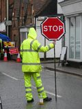 Trabajador de sexo masculino del camino con la chaqueta amarilla y los pantalones fluorescentes que llevan a cabo la muestra roja imagenes de archivo