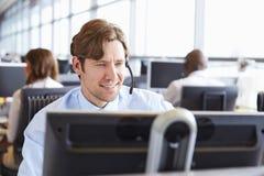 Trabajador de sexo masculino del centro de llamada, mirando la pantalla, primer Imagenes de archivo