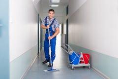 Trabajador de sexo masculino feliz con el pasillo de la oficina de la limpieza de la escoba imagen de archivo