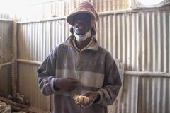 Trabajador de sexo masculino joven africano en una fábrica del recuerdo en el distrito más pobre de Nairobi - Kibera fotos de archivo libres de regalías