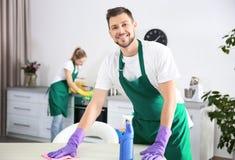 Trabajador de sexo masculino joven del servicio de la limpieza que trabaja en cocina fotografía de archivo libre de regalías