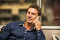 Trabajador de sexo masculino joven que habla en el teléfono fotografía de archivo
