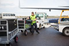 Trabajador de sexo masculino que coloca el equipaje en remolque en pista Foto de archivo libre de regalías