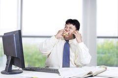 Trabajador de sexo masculino que come la hamburguesa en la oficina Fotos de archivo libres de regalías